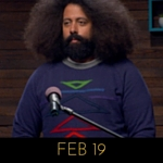 Image of Reggie Watts wearing a navy sweater with different coloured triangles on it, on Comedy Bang! Bang!