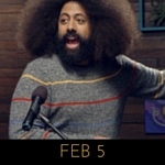 Image of Reggie Watts wearing a charcoal sweater with thin red, blue, and yellow stripes on Comedy Bang! Bang!