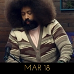 Image of Reggie Watts wearing a sweater that looks like an abstraction of a desert on Comedy Bang! Bang!