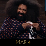 Image of Reggie Watts wearing a navy sweater with tiny birds on it, on Comedy Bang! Bang!