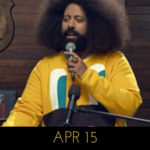 Image of Reggie Watts wearing a yellow sweater with a cartoon happy face on it, on Comedy Bang! Bang!