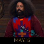 Image of Reggie Watts wearing a burgundy sweater with vibrant coloured stripes on it, on Comedy Bang! Bang!