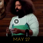 Image of Reggie Watts wearing a sweater with a robot space cat (or maybe a drone) on it, on Comedy Bang! Bang!