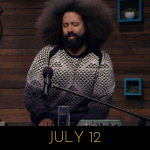 Image of Reggie Watts wearing black and white and grey half-square triangles, on Comedy Bang! Bang!