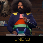 Image of Reggie Watts wearing a sweater with a spaceship on it, on Comedy Bang! Bang!